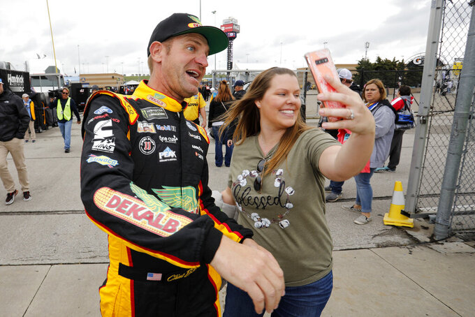 Clint Bowyer, left, poses for a picture with Brittany Goldsmith, right, before qualifying for a NASCAR Cup Series auto race at Kansas Speedway in Kansas City, Kan., Saturday, Oct. 19, 2019. (AP Photo/Colin E. Braley)