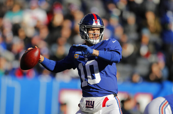 FILE - In this Dec. 15, 2019, file photo, New York Giants quarterback Eli Manning looks to pass in the first half of an NFL football game against the Miami Dolphins in East Rutherford, N.J. When two-time Super Bowl MVP Manning walked away from the Giants in January 2020 after a 16-year career, he really had no plans. As a quarterback, he had prepared for every contingency on the field. Retirement was foreign to him , and somewhat of a welcome relief. (AP Photo/Adam Hunger, File)