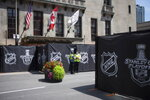"Security guards stand by at a section of the street outside Toronto's Royal York hotel, which is closed off as NHL teams arrive at the ""bubble"" ahead of the return of the league's season following a disruption due to the COVID-19 pandemic, in Toronto, Sunday, July 26, 2020. (Chris Young/The Canadian Press via AP)"