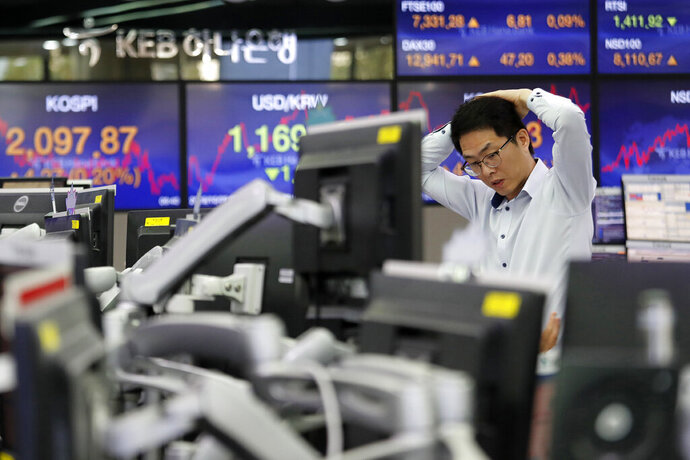 A currency trader watches monitors at the foreign exchange dealing room of the KEB Hana Bank headquarters in Seoul, South Korea, Tuesday, Oct. 29, 2019. Shares were mixed in Asia and Chinese benchmarks fell Tuesday after the S&P 500 index closed at an all-time high. (AP Photo/Ahn Young-joon)