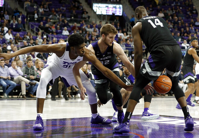 TCU center Kevin Samuel (21) loses control of the ball to Kansas State forward Dean Wade (32) and Makol Mawien (14) in the second half of an NCAA college basketball game in Fort Worth, Texas, Monday, March 4, 2019. (AP Photo/Tony Gutierrez)