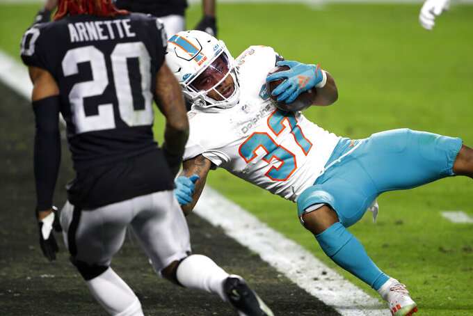 Miami Dolphins running back Myles Gaskin (37) scores a touchdown against the Las Vegas Raiders during the second half of an NFL football game, Saturday, Dec. 26, 2020, in Las Vegas. (AP Photo/Steve Marcus)