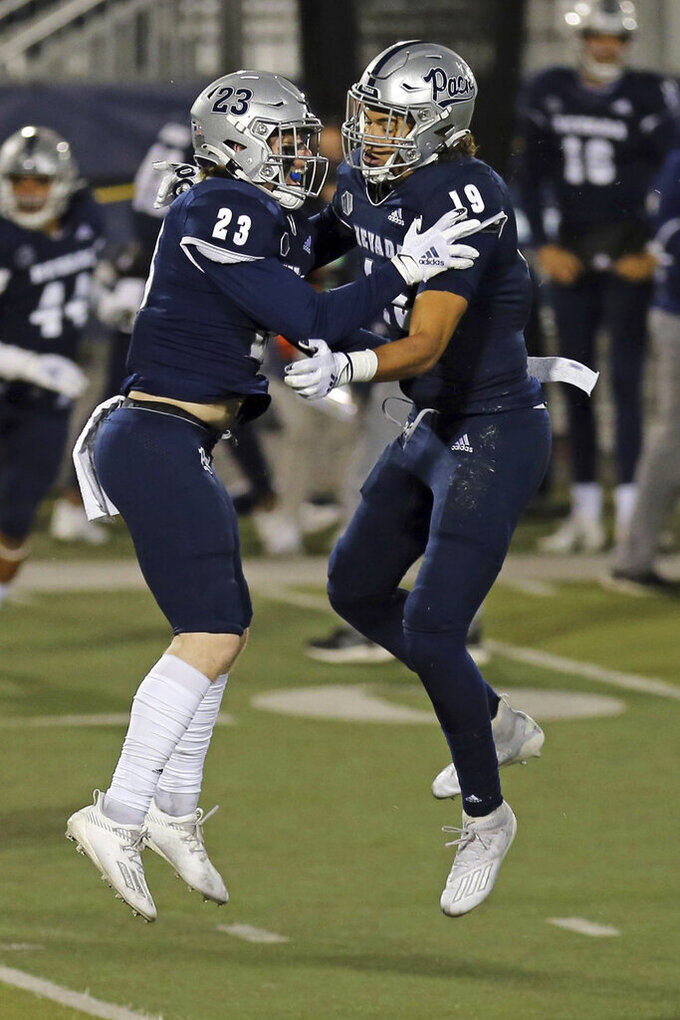 Nevada's Jack Powers (23) greets tight end Cole Turner (19) after Turner scored against Fresno State during the first half of an NCAA college football game Saturday, Dec. 5, 2020, in Reno, Nev. (AP Photo/Lance Iversen)
