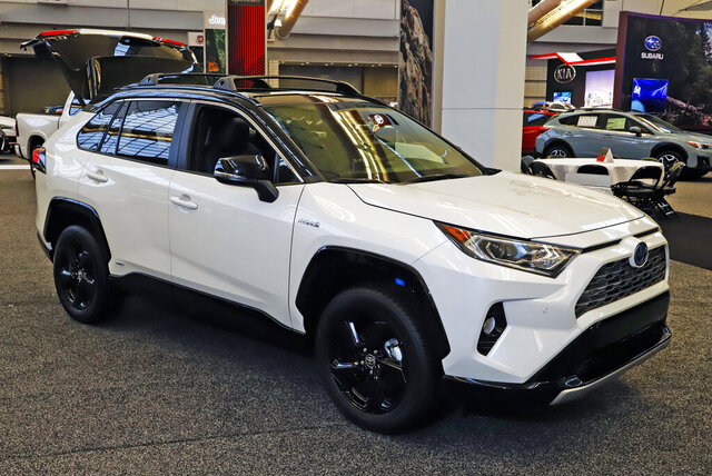 FILE - This Feb. 13, 2020 photo shows a 2020 Toyota RAV4 Hybrid on display at the 2020 Pittsburgh International Auto Show in Pittsburgh.  The Toyota RAV4 Hybrid and Honda CR-V Hybrid are similar in fuel economy, power and practicality according to Edmunds. Each is a smart buy for a fuel-efficient SUV. (AP Photo/Gene J. Puskar, File).