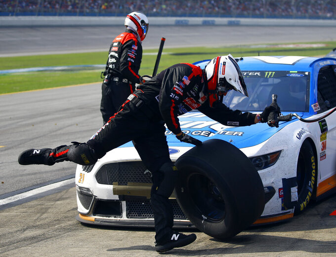 A crew member of Paul Menard trips over the tire as he runs back to the wall during a NASCAR Cup Series auto race at Talladega Superspeedway, Sunday, April 28, 2019, in Talladega, Ala. (AP Photo/Butch Dill)