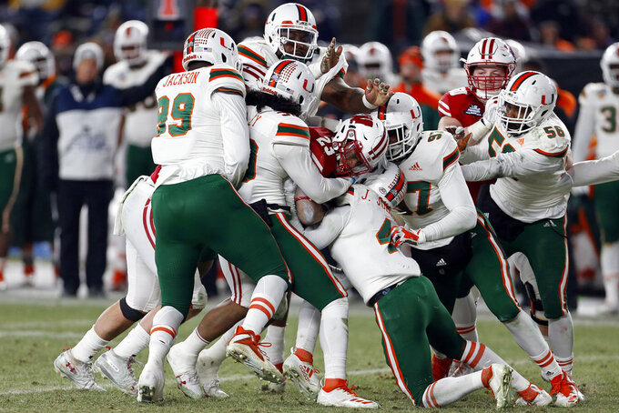 Wisconsin running back Jonathan Taylor (23) is tackled by several Miami players during the first half of the Pinstripe Bowl NCAA college football game Thursday, Dec. 27, 2018, in New York. (AP Photo/Adam Hunger)