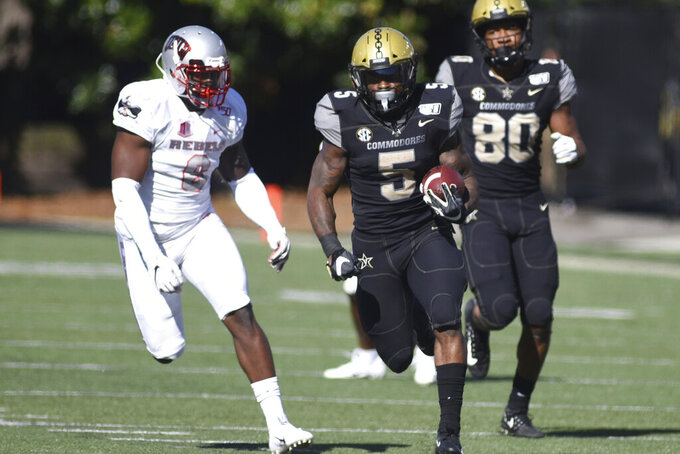 Vanderbilt running back Ke'Shawn Vaughn runs with the ball past UNLV linebacker Rayshad Jackson after a catch in the first half of an NCAA college football game Saturday, Oct. 12, 2019, in Nashville, Tenn. (AP Photo/Mike Strasinger)