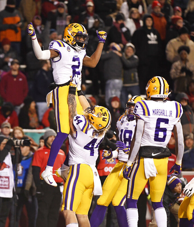 LSU receiver Justin Jefferson (2) celebrates with teammates Tory Carter (44) Foster Moreau (18) and Terrace Marshall Jr. (6) after scoring a touchdown against Arkansas during the first half of an NCAA college football game, Saturday, Nov. 10, 2018, in Fayetteville, Ark. (AP Photo/Michael Woods)
