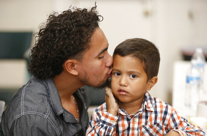 CORRECTS SON'S AGE TO 4, NOT 3 - Roger Ardino 24, gives his son Roger Ardino Jr., 4, a kiss on the cheek shortly after speaking to reporters at a news conference at the Annunciation House in El Paso, Texas, Wednesday, July 11, 2018. Ardino and Pablo Ortiz, 28, and his son Andres spoke to the media about their experiences while being detained and separated for several months from their sons. Tuesday night three fathers were reunited with their children but only two spoke this morning after the third, a father and daughter had already left El Paso early Wednesday morning. (Ruben R. Ramirez/The El Paso Times via AP)