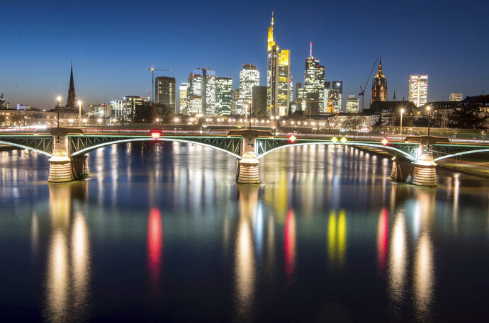 In this Feb. 13, 2018 photo the lights of the skyline of the Frankfurt, Germany, banking district are reflected in the river main after the sun set. (Boris Roessle/dpa via AP)