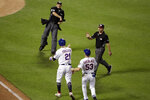 Home plate umpire Tripp Gibson, atop left, throws out New York Mets' Todd Frazier (21) during the fifth inning of a baseball game against the Philadelphia Phillies, Saturday, July 6, 2019, in New York. (AP Photo/Frank Franklin II)