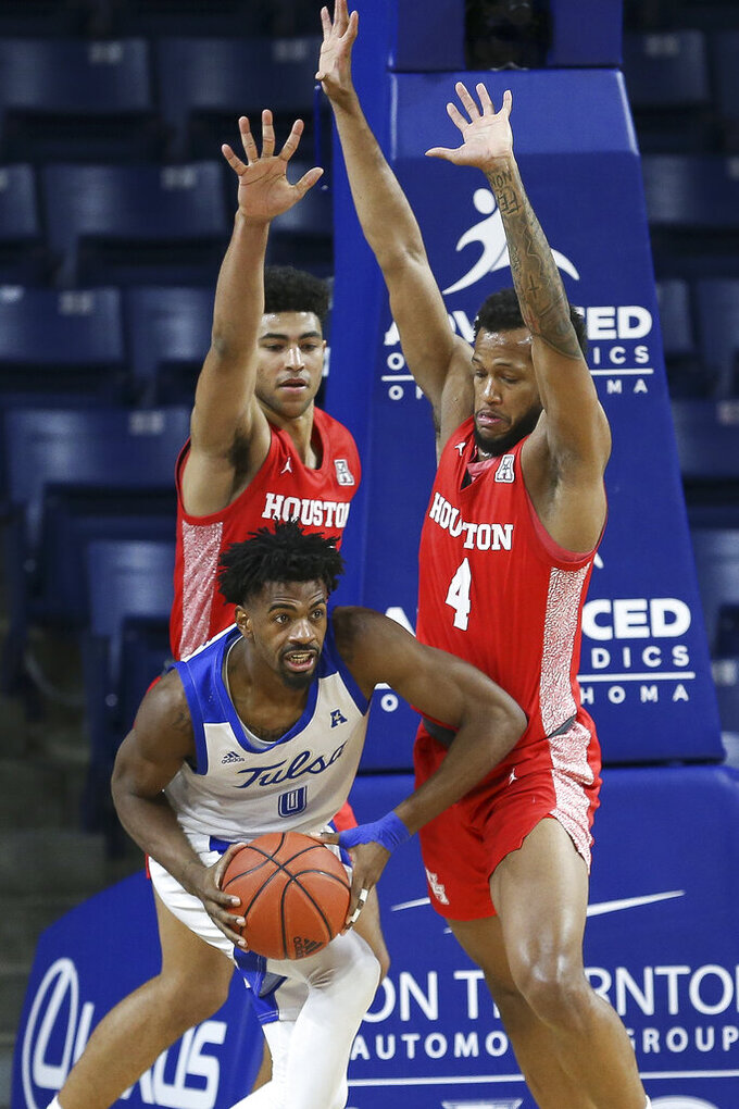 Tulsa's Curtis Haywood III grabs a rebound in front of Houston's Quentin Grimes and Justin Gorham (4) during the second half of an NCAA college basketball game in Tulsa, Okla. on Tuesday, Dec. 29, 2020. Tulsa won 65-64. (AP Photo/Dave Crenshaw)