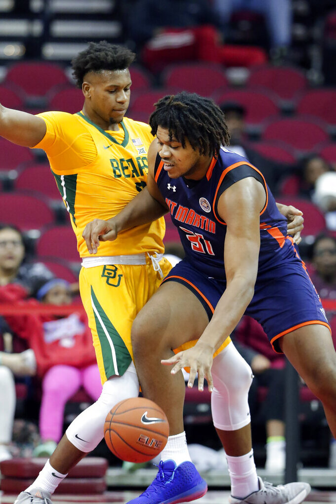 Tennessee-Martin center Jordan Pierce, right, drives into Baylor forward Flo Thamba, left, during the first half of an NCAA college basketball game Wednesday, Dec. 18, 2019, in Houston. (AP Photo/Michael Wyke)