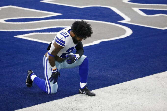 Dallas Cowboys running back Ezekiel Elliott (21) kneels in the end zone before the start of an NFL football game against the Atlanta Falcons in Arlington, Texas, Sunday, Sept. 20, 2020. (AP Photo/Ron Jenkins)