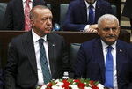 Turkey's President Recep Tayyip Erdogan, left, with Binali Yildirim, his mayoral candidate for Istanbul, attends parliament in Ankara, Turkey, Tuesday, June 25, 2019, two days after Ekrem Imamoglu, the candidate of the secular opposition Republican People's Party, won the election for mayor of Istanbul. Erdogan addressed his AK Party's weekly meeting, the first time he speaks since the Istanbul mayoral election Sunday, which was a big setback for him and his party. (AP Photo/Burhan Ozbilici)