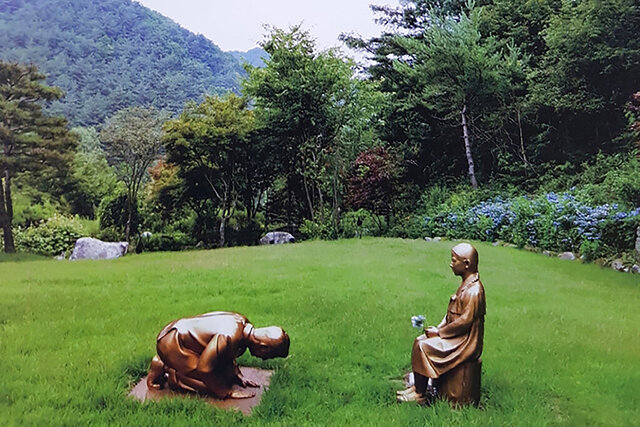 In this undated photo provided by The Korea Botanical Garden, statues of a man kneeling in front of a girl symbolizing victims of sexual slavery by Japan's World War II military at the Korea Botanical Garden in Pyeongchang, South Korea. The statue has become the latest subject of diplomatic sensitivity between the countries, with Tokyo's top government spokesman questioning whether the figure represents Prime Minister Shinzo Abe. (The Korea Botanical Garden via AP)
