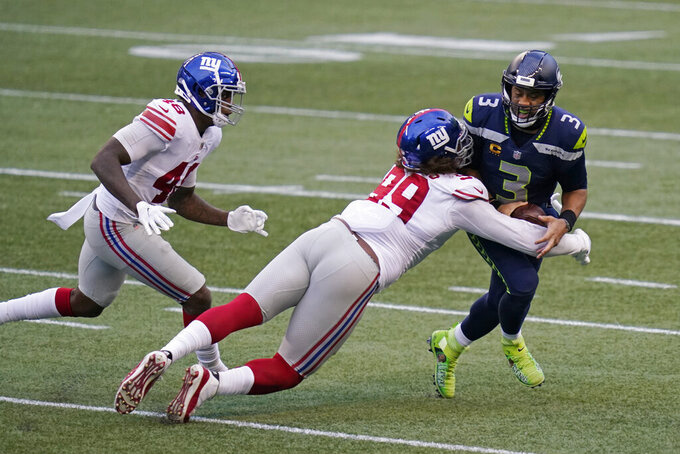 Seattle Seahawks quarterback Russell Wilson (3) is sacked by New York Giants defensive end Leonard Williams, center, as linebacker Tae Crowder (48) runs in to assist during the second half of an NFL football game, Sunday, Dec. 6, 2020, in Seattle. (AP Photo/Elaine Thompson)
