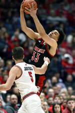 Louisville forward Jordan Nwora (33) grabs the ball in front of Western Kentucky guard Camron Justice (5) during the first half of an NCAA college basketball game Friday, Nov. 29, 2019, in Nashville, Tenn. (AP Photo/Mark Zaleski)