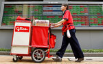A drink vendor moves past an electronic stock board of a securities firm in Tokyo, Thursday, June 14, 2018. Asian stock markets slumped on Thursday with South Koreans stocks plunging 1.6 percent on the first day of trading after an unprecedented summit between leaders of North Korea and the United States. Stocks plunged after Federal Reserved hiked its key rate and signaled an acceleration in its pace of rate increase. (AP Photo/Shuji Kajiyama)