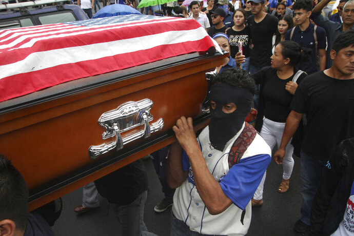In this Sunday, May 19, 2019 photo, an anti-government protester wearing a mask to hide his identity from security forces helps carry the U.S. flag-covered coffin of Eddy Montes Praslin to a church before his burial in Matagalpa, Nicaragua. Montes Praslin, a Nicaraguan-American dual national who died in a prison disturbance in Nicaragua, served in the U.S. Navy and was a staunch opponent of the government of President Daniel Ortega, according to his cousin Marvin Montes. (AP Photo/Oscar Duarte)