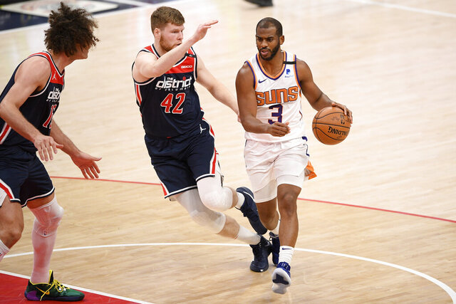Phoenix Suns guard Chris Paul (3) dribbles next to Washington Wizards forward Davis Bertans (42) and center Robin Lopez (15) during the first half of an NBA basketball game, Monday, Jan. 11, 2021, in Washington. (AP Photo/Nick Wass)