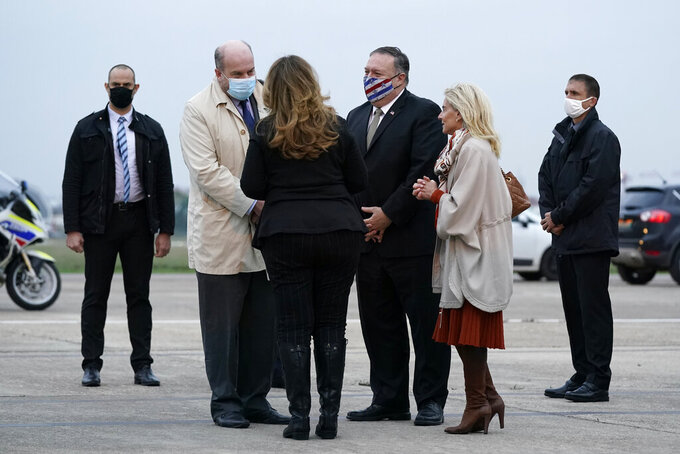 U.S. Secretary of State Mike Pompeo, third from right, and his wife Susan, third from left, speak with Jacques Jouslin de Noray of France's Ministry of Foreign Affairs, second from left, and U.S. Ambassador to France Jamie McCourt, second from right, after stepping off a plane at Paris Le Bourget Airport, Saturday, Nov. 14, 2020, in Le Bourget, France. Pompeo is beginning a 10-day trip to Europe and the Middle East. (AP Photo/Patrick Semansky, Pool)