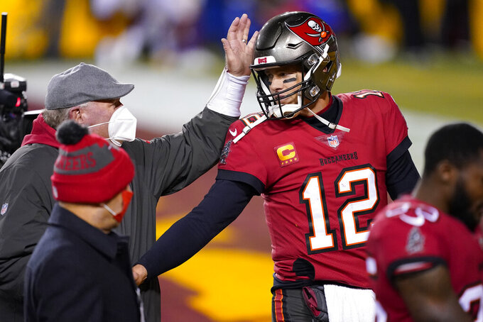 Tampa Bay Buccaneers head coach Bruce Arians, left, pats quarterback Tom Brady's helmet at the end an NFL wild-card playoff football game against the Washington Football Team, Saturday, Jan. 9, 2021, in Landover, Md. Tampa Bay won 31-23. (AP Photo/Andrew Harnik)