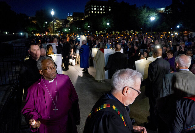 FILE - In this Thursday, May 24, 2018 file photo, The Most Rev. Michael Curry, left, the presiding bishop of the U.S. Episcopal Church and others take part in a candlelight vigil outside the White House in Washington. As a nation shaken by political divisions prepares to inaugurate a new president on Wednesday, Jan. 20, 2021, a group of Christian leaders, including Curry, are preparing to meet the tense moment with prayer during three days of ecumenical, nonpartisan programming organized under the umbrella of #PeaceWithJustice. (AP Photo/Andrew Harnik, File)