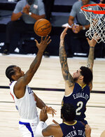Los Angeles Clippers' Kawhi Leonard, left, goes up against New Orleans Pelicans' Lonzo Ball, top right, during an NBA basketball game Saturday, Aug. 1, 2020, in Lake Buena Vista, Fla. (Kevin C. Cox/Pool Photo via AP)