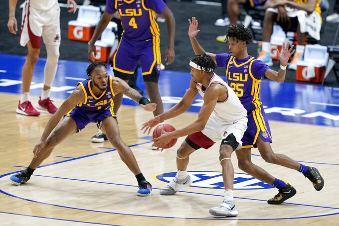 Arkansas' Moses Moody, center, is defended by LSU's Ja'Vonte Smart (1) and Eric Gaines (25) in the first half of an NCAA college basketball game in the Southeastern Conference Tournament Saturday, March 13, 2021, in Nashville, Tenn. (AP Photo/Mark Humphrey)