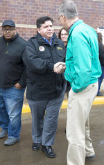"""FILE--In this March 20, 2019 file photo, Gov. J.B. Pritzker, center, speaks with Bill Hadley, the Stephenson County Board Chairman, right, and Pastor Antwon Funches of St. Paul Missionary Baptist Church, left, during a stop to survey flood damage in Freeport, Ill.  During his first six weeks in office, Pritzker's appointment calendar includes 70 """"attire"""" recommendations for events as varied as bill signings, a state police officer's funeral, a White House dinner, surveying flood damage, and cocktails with legislators at the Illinois Governor's Mansion.   (Scott P. Yates/Rockford Register Star via AP, File)"""