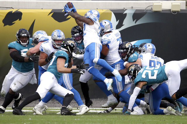 Detroit Lions running back D'Andre Swift, center, leaps over the line for a 1-yard touchdown against the Jacksonville Jaguars during the first half of an NFL football game, Sunday, Oct. 18, 2020, in Jacksonville, Fla. (AP Photo/Stephen B. Morton)