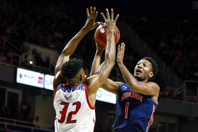 Auburn guard Jamal Johnson (1) puts up a shot over South Alabama forward Josh Ayeni (32) during the first half of an NCAA college basketball game, Tuesday, Nov. 12, 2019, in Mobile, Ala. (AP Photo/Butch Dill)