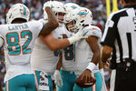Miami Dolphins quarterback Tua Tagovailoa, right, is congratulated by teammates after his touchdown during the first half of an NFL football game against the New England Patriots, Sunday, Sept. 12, 2021, in Foxborough, Mass. (AP Photo/Winslow Townson)