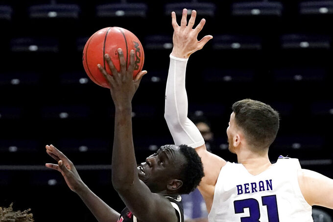 Nebraska forward Lat Mayen, left, drives to the basket past Northwestern forward Robbie Beran during the first half of an NCAA college basketball game in Evanston, Ill., Sunday, March 7, 2021. (AP Photo/Nam Y. Huh)