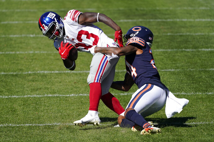 New York Giants running back Dion Lewis (33) tries to break free from Chicago Bears cornerback Buster Skrine (24) during the second half of an NFL football game in Chicago, Sunday, Sept. 20, 2020. (AP Photo/Charles Rex Arbogast)