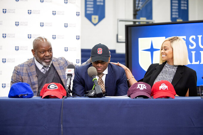 Jesuit senior running back EJ Smith, son of NFL all-time leading rusher Emmitt Smith, is congratulated by his parents Emmitt and Pat Smith as he gives a live interview on ESPN after announcing his commitment to play football at Stanford University during a signing day ceremony, Wednesday, Dec. 18, 2019 at Jesuit College Preparatory School in Dallas. (Jeffrey McWhorter/The Dallas Morning News via AP)
