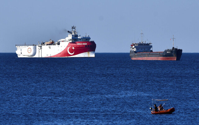 In this photograph taken from the Mediterranean shores near the city of Antalya, Turkey, a merchant ship, top right, sails past the research vessel Oruc Reis, Thursday, July 23, 2020. Greece has warned Thursday it will do