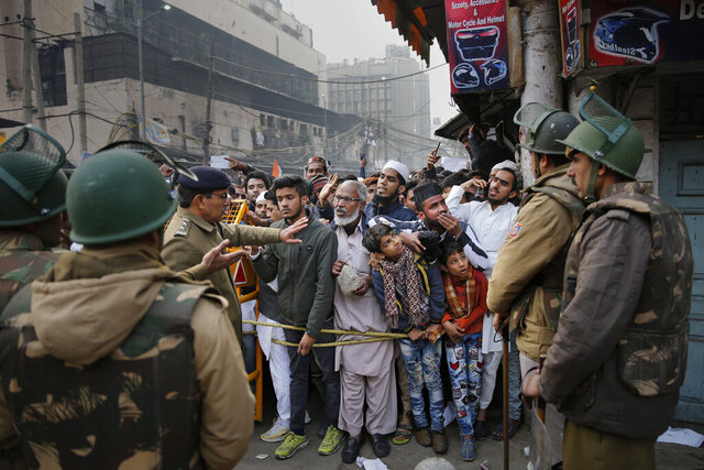 Indian policemen stop protesters at a police barricade in New Delhi, India, Friday, Dec. 20, 2019. Police banned public gatherings in parts of the Indian capital and other cities for a third day Friday and cut internet services to try to stop growing protests against a new citizenship law that have so far left more than 10 people dead and more than 4,000 others detained. (AP Photo/Altaf Qadri)