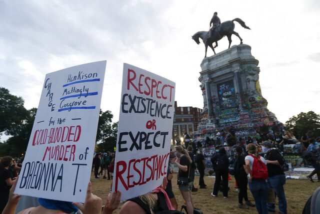 EDS NOTE: OBSCENITY - FILE - In this Tuesday June 23, 2020, file photo protesters gather near the statue of Confederate General Robert E. Lee on Monument Avenue in Richmond, Va. Just a little over a month ago, the area around Richmond's iconic statue of Confederate Gen. Robert E. Lee was as quiet and sedate as the statue itself.  But since the May 25 police killing of George Floyd in Minneapolis, the area has been transformed into a bustling hub of activity for demonstrators protesting against police brutality and racism. (AP Photo/Steve Helber, FILE)