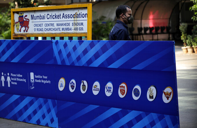 A security guard wearing a face mask as a precaution against the coronavirus stands next to a hoarding displaying logos of teams participating in Indian Premier League 2021, outside Wankhede Stadium in Mumbai, India, Tuesday,  May 4, 2021. The Indian Premier League was suspended indefinitely on Tuesday after players or staff at three clubs tested positive for COVID-19 as nationwide infections surged. (AP Photo/Rajanish kakade)
