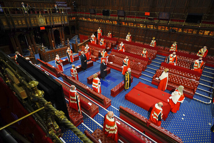 Members stand in the House of Lords in the Palace of Westminster, London, for the arrival of Queen Elizabeth II at the State Opening of Parliment, Tuesday May 11, 2021. (Aaron Chown/Pool via AP)