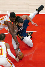 New Orleans Pelicans center Steven Adams (12) and Atlanta Hawks center Clint Capela (15) chase a loose ball in the first half of an NBA basketball game Tuesday, April 6, 2021, in Atlanta. (AP Photo/John Bazemore)