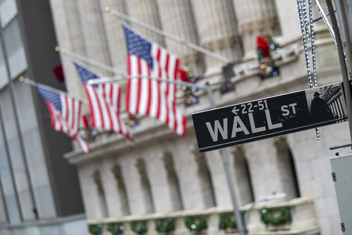 FILE - In this Jan. 3, 2020 file photo, the Wall St. street sign is framed by American flags flying outside the New York Stock Exchange in New York.  Stocks are falling early on Wall Street Thursday, Sept. 17,  as the late selling from the previous day carries over.  (AP Photo/Mary Altaffer, File)