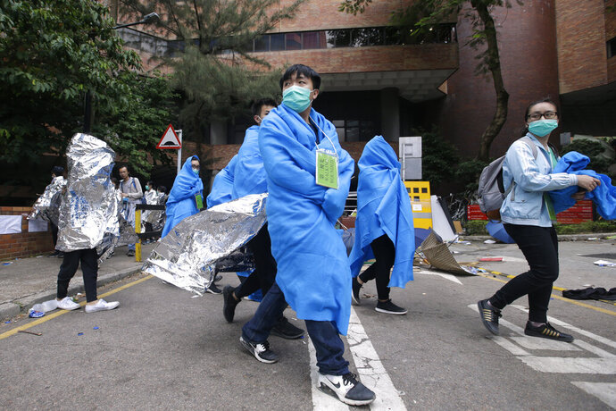 Injured protesters wrapped in blankets, walk through the campus of the Hong Kong Polytechnic University in Hong Kong, Tuesday, Nov. 19, 2019. About 100 anti-government protesters remained holed up at the Hong Kong university Tuesday as a police siege of the campus entered its third day. (AP Photo/Achmad Ibrahim)