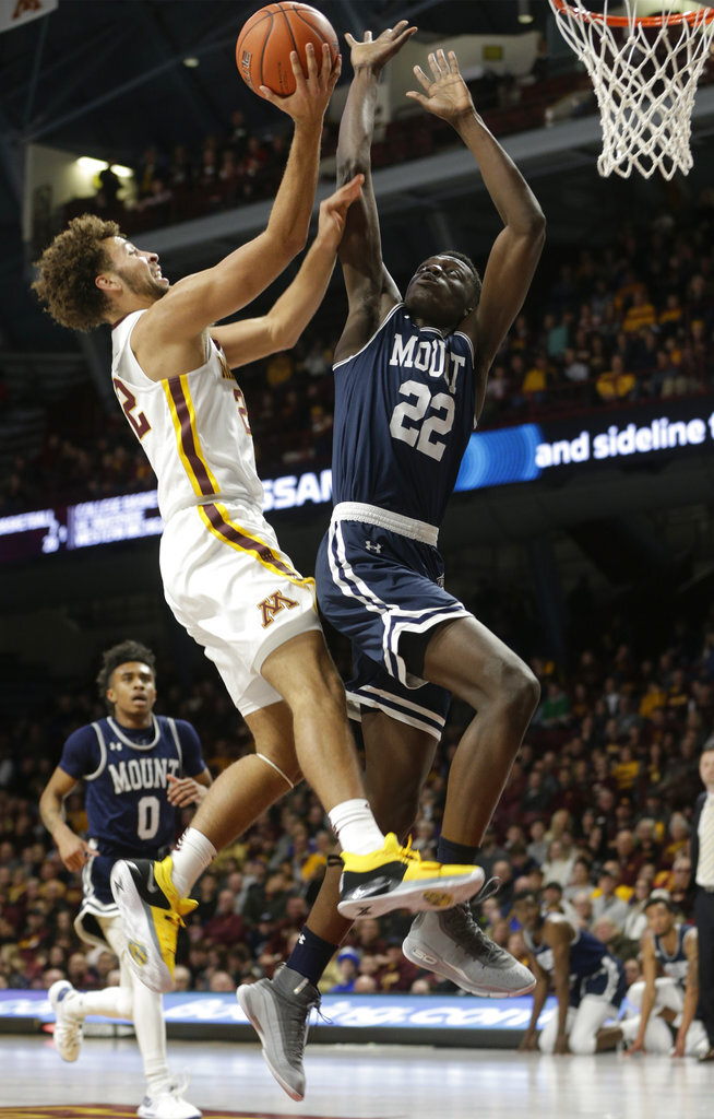 Minnesota guard Gabe Kalscheur, front left,shoots against Mount St. Mary's forward Nana Opoku, front right, during the first half of an NCAA basketball game Sunday, Dec. 30, 2018, in Minneapolis. (AP Photo/Paul Battaglia)