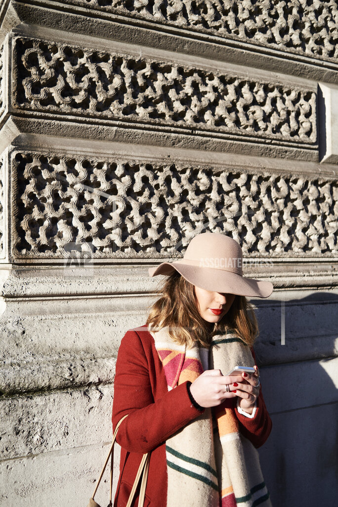 Stylish woman at a building wearing a floppy hat using cell phone