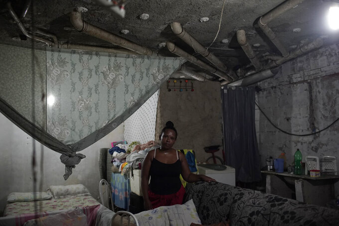FILE - In this Jan. 13, 2021 file photo, Ana Paula de Santos poses for a photo inside a room that she occupies with her husband in a building that used to house a factory, amid the new coronavirus pandemic, in Rio de Janeiro, Brazil. De Santos, who worked as a maid, has been unable to work because of COVID-19 and says that she can't afford the cost of living after the Brazilian government cut off financial aid to poor families affected by the pandemic. (AP Photo/Silvia Izquierdo, File)