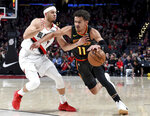 Atlanta Hawks guard Trae Young, right, drives to the basket on Portland Trail Blazers guard Seth Curry during the first half of an NBA basketball game in Portland, Ore., Saturday, Jan. 26, 2019. (AP Photo/Steve Dykes)
