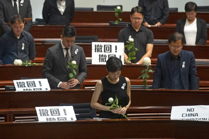 Pro-democracy lawmakers pay a silent tribute to the man who fell to his death on Saturday evening after hanging a protest banner on scaffolding on a shopping mall, at the Legislative Council in Hong Kong, Wednesday, June 19, 2019. Hong Kong lawmakers are meeting for the first time in a week, after massive protests over an extradition bill that eventually was suspended. The placards with Chinese read